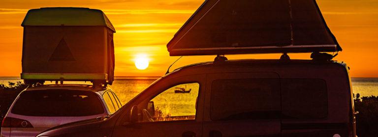 Autos mit Dachzelten bei Sonneruntergang