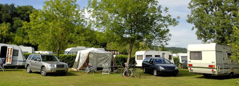 Mehrere Wohnwagen und Autos auf einem begrünten Campingplatz im Sommer