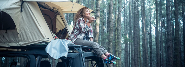 Eine Frau sitzt mit einen Getränk im Eingang Ihres Dachzeltes auf Ihrem Auto und lässt die Füße baumeln