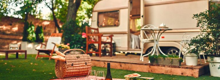 Wohnwagen mit Terrasse und davor liegendem Picknick-Platz