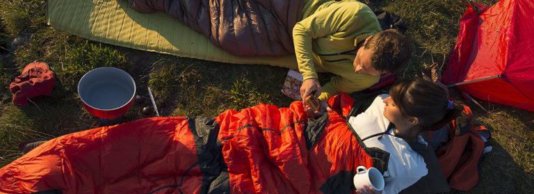 Zwei Personen liegen in Ihrem Schlafsäcken auf einer Wiese